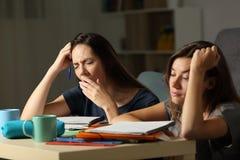 Estudiantes cansados que estudian en la noche en casa Imagenes de archivo