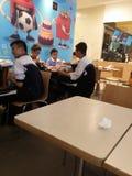Estudiantes chinos de la escuela secundaria en el restaurante del ` s de McDonald Foto de archivo