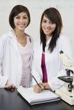 Estudiantes con el microscopio en laboratorio de ciencia Foto de archivo