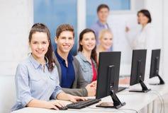 Estudiantes con el monitor de computadora en la escuela Imagen de archivo libre de regalías