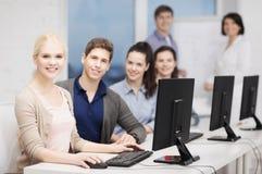 Estudiantes con el monitor de computadora en la escuela Fotos de archivo libres de regalías