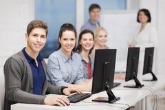 Estudiantes con el monitor de computadora en la escuela Fotos de archivo