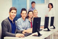 Estudiantes con el monitor de computadora en la escuela Foto de archivo libre de regalías