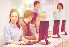 Estudiantes con el monitor de computadora en la escuela Imagen de archivo