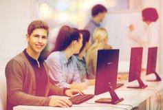Estudiantes con el monitor de computadora en la escuela Imagenes de archivo