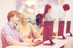 Estudiantes con el monitor de computadora en la escuela Imágenes de archivo libres de regalías
