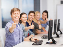 Estudiantes con el monitor de computadora que muestra los pulgares para arriba Foto de archivo