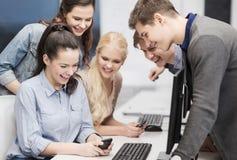 Estudiantes con el monitor de computadora y smartphones Fotografía de archivo