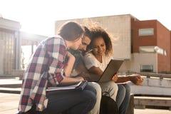 Estudiantes con el ordenador portátil en campus Imagen de archivo libre de regalías