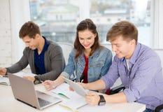 Estudiantes con el ordenador portátil, los cuadernos y PC de la tableta Fotos de archivo