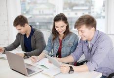 Estudiantes con el ordenador portátil, los cuadernos y PC de la tableta Imagen de archivo