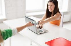 Estudiantes con el ordenador portátil que comparte la calculadora en la escuela Fotografía de archivo libre de regalías