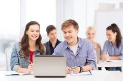 Estudiantes con el ordenador portátil y los cuadernos en la escuela Fotos de archivo