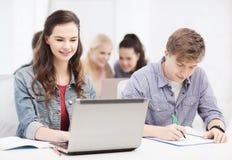 Estudiantes con el ordenador portátil y los cuadernos en la escuela Fotografía de archivo libre de regalías