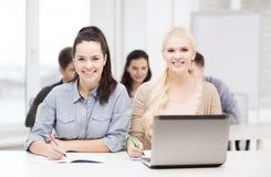 Estudiantes con el ordenador portátil y los cuadernos en la escuela Imagenes de archivo