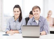 Estudiantes con el ordenador portátil y los cuadernos en la escuela Imagen de archivo libre de regalías