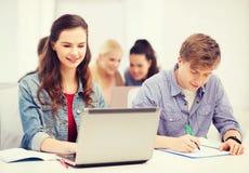 Estudiantes con el ordenador portátil y los cuadernos en la escuela Fotos de archivo libres de regalías