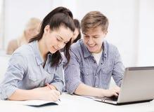 Estudiantes con el ordenador portátil y los cuadernos en la escuela Fotografía de archivo