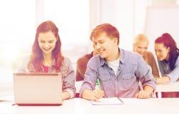 Estudiantes con el ordenador portátil y los cuadernos en la escuela Imágenes de archivo libres de regalías