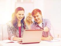Estudiantes con el ordenador portátil y los cuadernos en la escuela Imagen de archivo