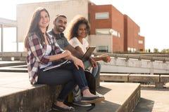 Estudiantes con el ordenador portátil en campus Fotos de archivo