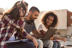 Estudiantes con el ordenador portátil en campus Imágenes de archivo libres de regalías