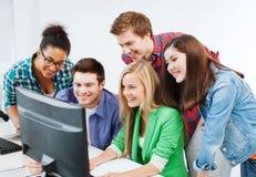 Estudiantes con el ordenador que estudian en la escuela Foto de archivo libre de regalías