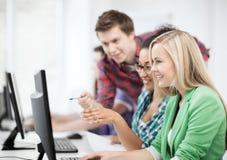 Estudiantes con el ordenador que estudian en la escuela Fotos de archivo libres de regalías