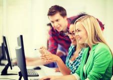 Estudiantes con el ordenador que estudian en la escuela Imagenes de archivo