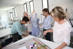 Estudiantes con el profesor en clase de la modistería Foto de archivo libre de regalías