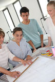 Estudiantes con el profesor en clase de la modistería Foto de archivo