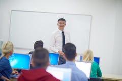 Estudiantes con el profesor en classrom del laboratorio del ordenador Foto de archivo libre de regalías