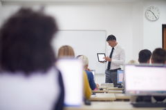 Estudiantes con el profesor en classrom del laboratorio del ordenador Fotografía de archivo libre de regalías