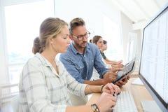 Estudiantes con el profesor que trabaja en el ordenador Imagen de archivo libre de regalías