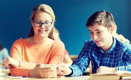 Estudiantes con el smartphone que manda un SMS en la escuela Imágenes de archivo libres de regalías