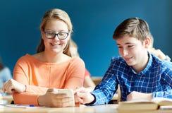 Estudiantes con el smartphone que manda un SMS en la escuela Imagen de archivo