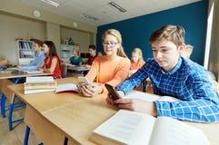 Estudiantes con el smartphone que manda un SMS en la escuela Fotografía de archivo libre de regalías