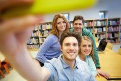 Estudiantes con el smartphone que toma el selfie en biblioteca Fotos de archivo