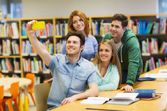Estudiantes con el smartphone que toma el selfie en biblioteca Fotografía de archivo
