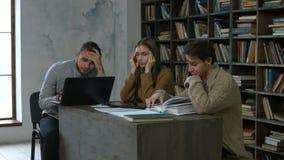 Estudiantes con exceso de trabajo que estudian en biblioteca del campus almacen de video