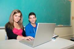 Estudiantes con la computadora portátil en sala de clase Imagen de archivo libre de regalías