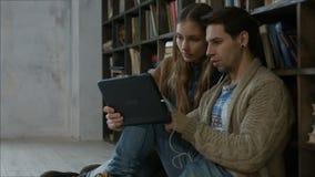 Estudiantes con la tableta digital que estudian junto metrajes