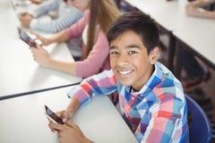 Estudiantes con la tableta digital y el teléfono móvil en sala de clase Fotografía de archivo libre de regalías