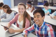 Estudiantes con la tableta y el ordenador portátil digitales en sala de clase Fotografía de archivo