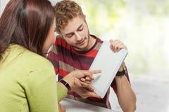 Estudiantes con la tableta y los cuadernos digitales Imagen de archivo