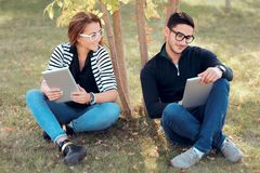 Estudiantes con las tabletas de Digitaces que se sientan en hierba en campus universitario foto de archivo libre de regalías