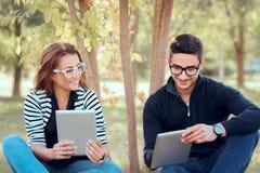 Estudiantes con las tabletas de Digitaces que se sientan en hierba en campus universitario foto de archivo