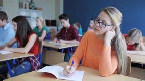 Estudiantes con los cuadernos que escriben la prueba en la escuela metrajes