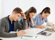Estudiantes con los cuadernos y PC de la tableta en la escuela Imagenes de archivo