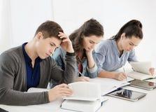 Estudiantes con los cuadernos y PC de la tableta en la escuela Imágenes de archivo libres de regalías